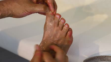 mal cheiroso : Adult white caucasian man checks athletes foot between toes in bath. Zoom foot fungus between toes.