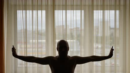 pozisyon : Silhouette of man standing and stretching in front of orange yellow curtains window morning indoors city.