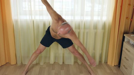 tilts : White man doing exercise at home. Morning warm up stretching. Yoga individual.