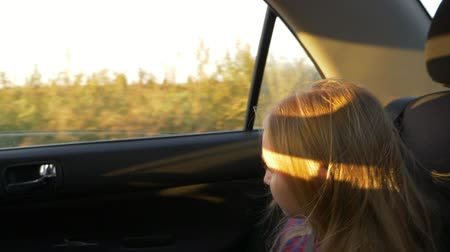 waggle : Little caucasian girl traveling in car. Car bounce and shake very much. Handheld shot close up.