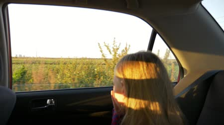 седые волосы : Young girl traveling by car summer evening. Rural scene at window. Focus to background. Unfocused girl close up handheld shot. Стоковые видеозаписи