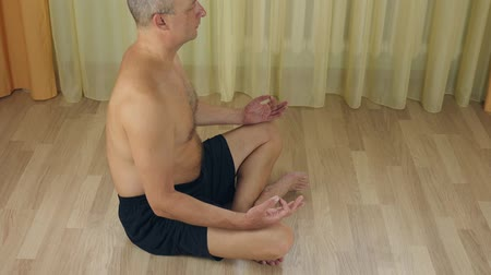 respiração : Adult bald man sitting on floor, meditating in lotus yoga pose, concentrating in silence, observing breath, relaxing mind, soul and body. Calm men trying to reach Zen harmony Vídeos