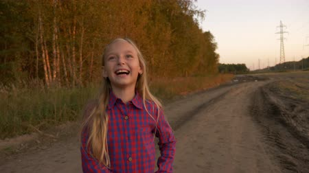 vigyorgó : Happy young girl play at country road and show thumbs up gestures. White girl jumping up at sunset.