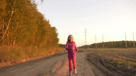 vigyorgó : Happy young caucasian girl jumping by country road. White caucasian girl happy laughing.