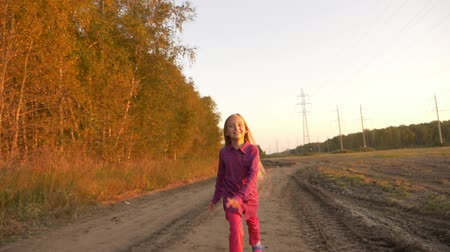 looking far away : Young caucasian girl running jumping by country road. White blonde long hair girl jumping outdoors.