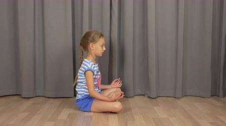 ruhanilik : Young girl sitting in zen pose on floor at living room and meditating. Girl do practice of yoga. Stok Video