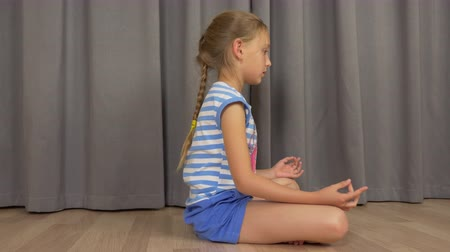 pozisyon : Young girl sitting in zen pose on floor at living room and meditating. Girl do practice of yoga. Stok Video