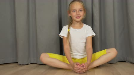 żart : Young girl do yoga butterfly pose. White girl stretchin at living room indoors.