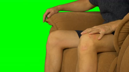 tenso : Male legs of a man sitting on a chair. Man is stroking his knees with his hand.