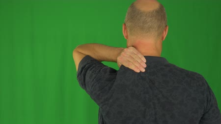arka görünüm : Man rubbing his shoulders with left hand. Back view waist up in polo shirt.