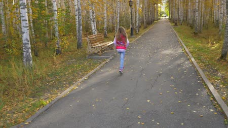 executar : Blonde girl with long hair runs down alley in autumn park. Slowed movement of hair swyings.
