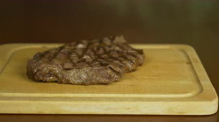 sál : Hand salt steak. The salt slowly falls on top of the meat. The meat lies on a wooden board.
