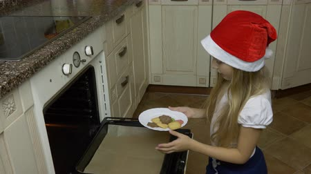 vigyorgó : A young white girl dropped the cookies from the plate to the oven. A girl in a red cap prepares for Christmas. The girl bakes ginger biscuits cookies.