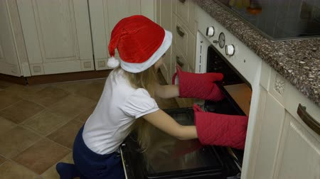 vigyorgó : Little girl opens the oven. Ginger cookies are taken from the oven. The girl cooked Christmas cookies. She sniffs cookies and enjoys the scent. Happy little girl is smiling and looking at the camera. Stock mozgókép