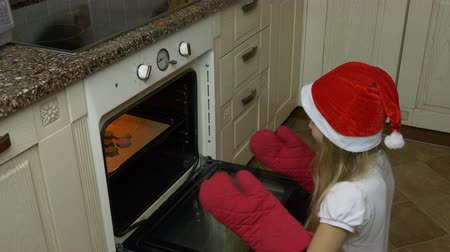 kolano : Track slide shot. Young girl claps hands and check cookies in oven. Girl bakes gingerbread cookie. Girl opens oven at kitchen and take out cookies for Christmas. Girl smiling and looking to camera. Wideo