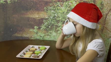 bandeja : Caucasian young girl in red hat sitting at table in home kitchen. Girl drink water or tea wrom white cup. Close up locked down shot. One person face. Stock Footage
