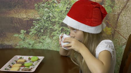 piada : Close up locked down handheld shot. Young caucasian girl in red cap hat drinking from white cup mug. The girl quenched her thirst before Christmas.