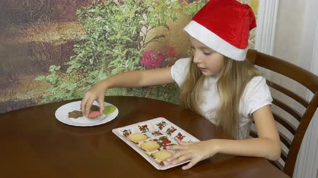 bandeja : Young blonde girl in red hat sitting by the table at home kitchen. The girl is preparing for Christmas and shifts the cookies from the plate to the tray. Ginger bread cookies bisquits.