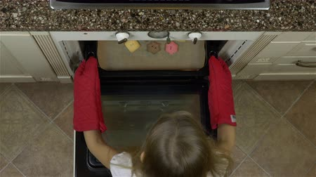 keksz : Girl take tray with biscuit ginger cookies from oven. Looking to top and smiling. Red mittens on her hands for protection from hot oven. Christmas coming. Stock mozgókép