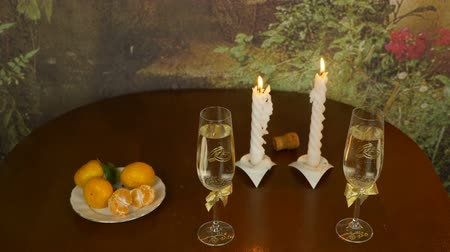 şarap kadehi : Romantic table for the newlyweds. Two glasses with sparkling wine. Two candles are hot. Bubbles sparkle and rise up in the wine glasses. The man blows out the candles. A stream of smoke rises.