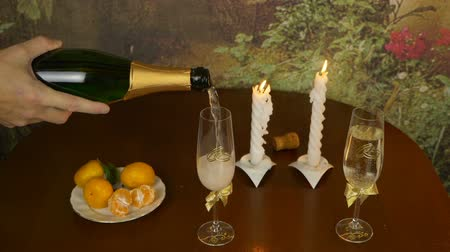 casado : Still life with wine and a snack on the table. The hand pours the champagne over the glasses. Rings are the symbol of the bride and groom. Mandarins are on the table.