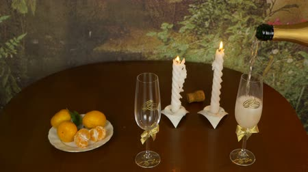 obiad : Pouring sparkling champagne wine into the glass against wooden background. Mandarins in plate on table. Light from pair candles. Evening indoors shot.