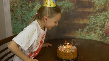 piada : Funny girl and her father can not blow birthday candles on cake. Joke party at home. Young girl with adult man blowing candles on cake. Lot of smoke and ash on table. Girl clapping. Fast motion effect