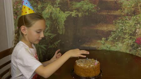 kilitlemek : The girl removes the candles from the cake. The girl pulls out candles from the cake standing on the table. Stok Video