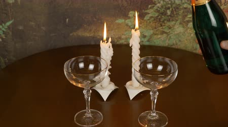 cera : Beginning of a romantic evening. On the table are two wine glasses and a bottle of champagne. Mans hand pours champagne on glasses. Hand with a lighter ignites the candles.