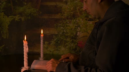 mech : Adult caucasian man sitting by table at night and read book with pair white candles.