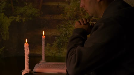 кавказский : Adult caucasian man reads a book. A burning candle, pair candles on the table. Warm evening indoors.