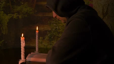 szerzetes : Burning candle in a small white candlestick . A monk in a hood reading a book . Selective focus. Got find evrika gestures. Stock mozgókép