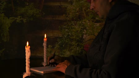 кавказский : Caucasian man businessman or student sitting at the table at night. Candlelight illuminate notebook. Man write to notebook with pen by hand. Night dark warm atmosphere. Man blow candles and go out. Стоковые видеозаписи
