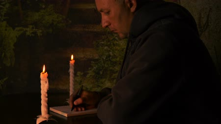рукопись : Student do homework at night with candles. Student writing in notebook with pen at dark night in candlelights. Стоковые видеозаписи