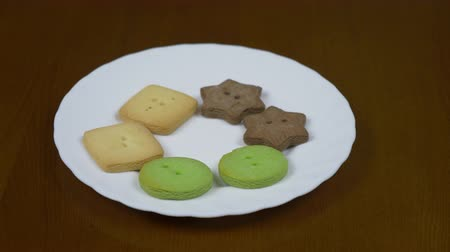pişmiş : White plate with colored ginger gingerbread cookies. Zoom in dolly track in close up indoors shot. Ginger cookies brown green and yellow color at plate on table.