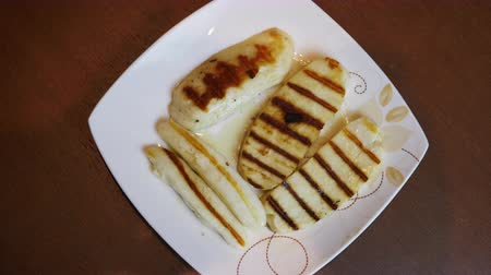 bulaşıklar : Grilled slices of halloumi cheese on plate top view rotate. Greek goat cheese grilled on beige plate. Stripes gold brown color. Food mediterian kitchen.