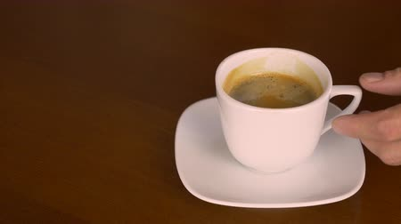grãos de café : Close up white cup of freshblack coffee espresso. Hand take coffee drink and put back on plate. Wooden table derk brown color. Coffee drinking concept for coffee lovers caf restorante barista. Vídeos