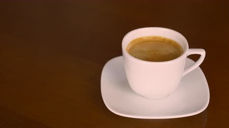 kahve molası : Man hand take cup of coffee from plate on table, drink and put cup of espresso back. White cup of americano. Black coffee espresso. Space for text. Locked down close up shot. Coffee break.