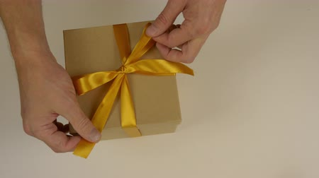 ajándékdobozban : Mens hands make a bow knot on a gift box made of gold satin ribbon. Cut the ends of the yellow ribbon with scissors. Decoration of the gift box for the holiday. Gift giving. Top view.
