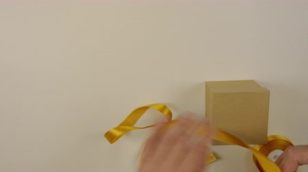 bola : Preparation for gift wrapping. A box of brown cardboard. Mens hands measure the gold satin ribbon to decorate the gift box. Top view close up.