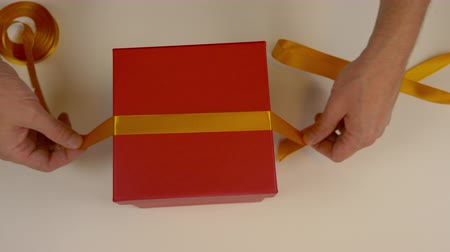 bola : Preparation for gift wrapping. A red box of cardboard. Mens hands measure the gold satin ribbon to decorate the gift box. Top view close up. Yellow tape.