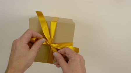 bola : Close up top view high angle. Mens hands straighten a gold bow from a satin ribbon on a gift box. Preparing for the gift giving event. Gift box with yellow bow. Brown carton box.