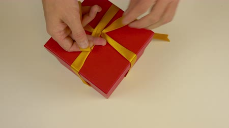 ajándékdobozban : Fast motion time lapse. Wrapping red gift box. Caucasian mans hands packing gift box. Mens hands tie a ribbon around a red cardboard box. Top view close up. Gold yellow tape ribbon.
