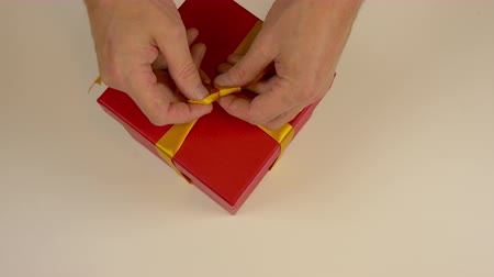 bola : Close up top view high angle. Mens hands straighten a gold bow from a satin ribbon on a gift box. Preparing for the gift giving event. Gift box with yellow bow. Red carton box. Vídeos