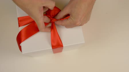 градация : Wrapping white gift box. Caucasian mans hands packing gift box. Mens hands tie a red ribbon around a white cardboard box. Top view close up. Red satin tape ribbon.