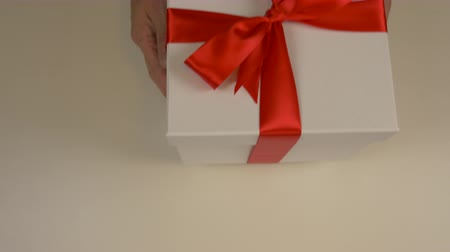 vysoký úhel pohledu : Caucasian man hands give the red gift box with gold ribbon bow. Hands take white gift box. Top view close up shot. White gift box. Dostupné videozáznamy