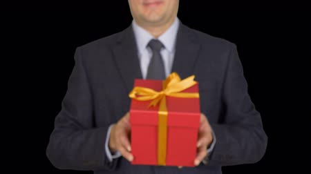 cavalheiro : A man in a business suit with a tie is holding a red gift box. A man gives a gift. A businessman with a gift in his hands. Green screen alpha channel transparent background. From unfocus to focus.