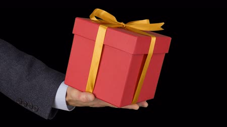 ajándékdobozban : Male man hand holds red gift box with gold bow. Celebrate eve present gift box. Caucasian man in classical suit. Alpha channel chroma key transparent background. Locked down.