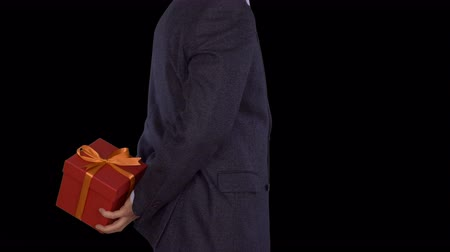 cavalheiro : A man in a business suit is holding a red gift box behind his back. Caucasian man shifts from foot to foot. Businessman gives a gift. Close up locked down shot. Alpha channel chroma key. Side view.