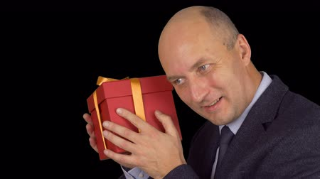 ajándékdobozban : Happy caucasian businessman get present. Red gift box with gold yellow bow. Man check gift box shaking. Close up locked down. Alpha channel chroma key transparent background. Prores 4444. Stock mozgókép